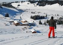 Großansicht Skifahrer auf der Piste vorm Almhotel